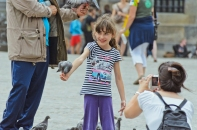 Amsterdam, The Netherlands: Pigeon eating out of girl's hand.