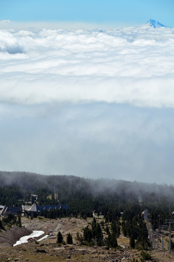 This photo captures Timberline Lodge beneath a blanket of clouds with Mount Jefferson peeking through the top of the cloud cover.