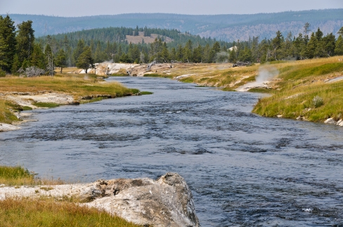 Firehole River and numerous geysers visible along the banks.